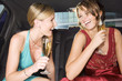 Two women drinking champagne in the back of a car