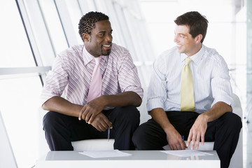 Two businessmen sitting in office lobby talking and smiling