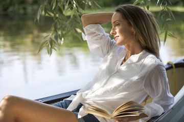 Young woman sitting in a boat reading a book