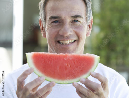 A man holding a slice of watermelon