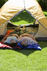Couple lying side by side on sleeping bags in tent entrance on garden lawn, smiling, rear view