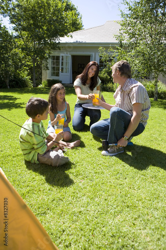 Family taking break from assembling tent on garden lawn, mother serving orange juice, smiling
