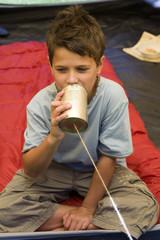 Boy (8-10) sitting on sleeping bag inside tent, speaking into tin can phone, front view