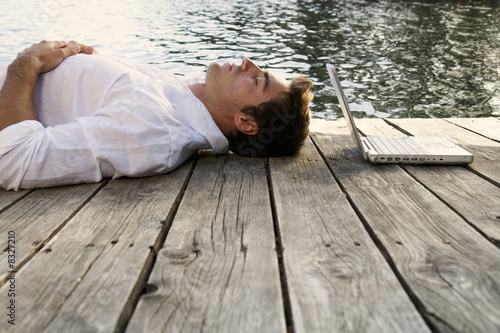 A young man with a laptop laying on a wooden jetty