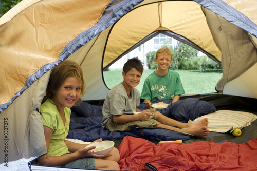 Three children (8-10) sitting inside tent on garden lawn, eating breakfast, smiling, portrait