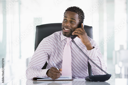 Businessman sitting in office with personal organizer open on te