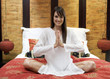 A woman sitting on a bed meditating