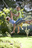 Boy and girl (8-10) swinging on garden rope swing, smiling, side view, portrait