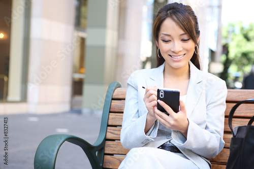 Asian Business Woman on Bench Outside Office