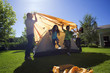Family assembling dome tent on garden lawn, parents placing orange outer canvas over tent frame, children (8-10) running out of way (backlit)