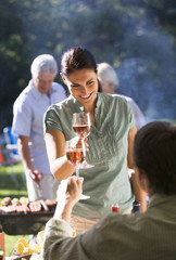 Family having barbecue in summer garden, focus on couple raising wine glasses in toast in foreground, smiling