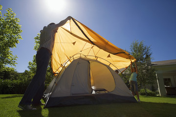 Father and children (8-10) assembling dome tent on garden lawn, placing orange outer canvas over tent frame, smiling, side view (backlit)