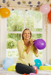 Woman preparing birthday party at home, inflating balloons on window seat, smiling, front view, portrait