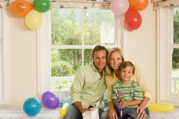 Boy (4-6) sitting with parents beside party balloons on window seat at home, holding birthday card, smiling, portrait