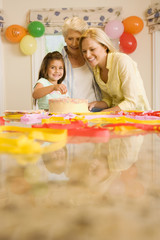 Girl (4-6) sitting at table beside birthday cake, mother and grandmother looking on, smiling, portrait (surface level)