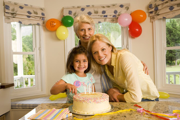 Girl (4-6) sitting with mother and grandmother at table beside birthday cake, smiling, portrait