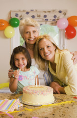 Girl (4-6) sitting with mother and grandmother at table beside birthday cake, making 'thumbs up' sign, smiling, portrait