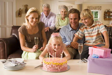 Three generation family sitting on sofa at home, girl (4-6) blowing out candles on birthday cake