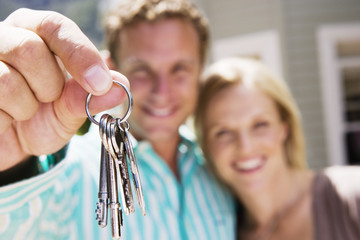 Couple standing in front of house, man holding aloft set of keys, smiling, close-up, portrait (differential focus)