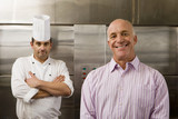 Male chef and restaurant manager standing in commercial kitchen, smiling, front view, portrait