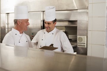 Two male chefs talking in commercial kitchen, mature man holding clipboard