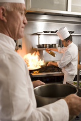 Chef frying food in flaming pan on gas hob in commercial kitchen, second chef carrying large pot, side view