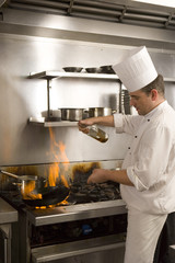 Chef pouring cooking oil into flaming pan on gas hob in commercial kitchen, side view