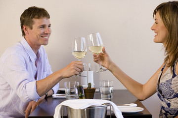 Couple sitting at restaurant table, raising wine glasses in toast, smiling, profile