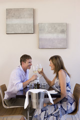 Couple sitting at restaurant table with ice bucket, raising wine glasses in toast, smiling, profile