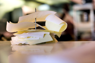 Stack of order checks on paper spindle in restaurant, close-up (differential focus, surface level)