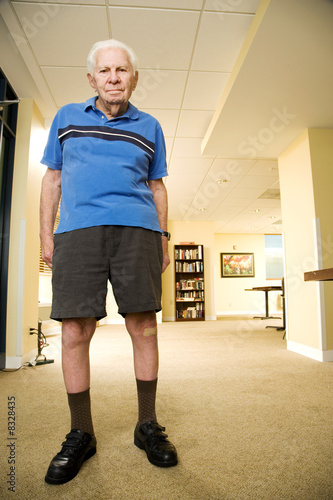 An elderly man wearing shorts