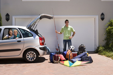 Father loading camping equipment into car boot on driveway, holding fishing rod, children (8-10) sitting in parked car, smiling, portrait