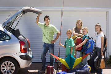 Family loading camping equipment into parked car boot on driveway, boy (8-10) holding fishing rod and kite, smiling, side view, portrait