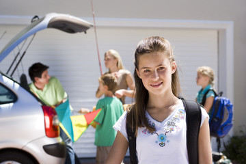 Family loading camping equipment into parked car boot on driveway, focus on girl (11-13) standing in foreground, smiling, portrait