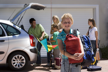 Family loading camping equipment into parked car boot on driveway, girl (8-10) carrying rucksack and sleeping bag in foreground, smiling, portrait