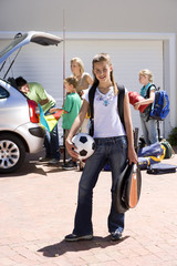 Family loading camping equipment into parked car boot on driveway, girl (11-13) carrying rucksack, soccer ball and tennis racquets in foreground, smiling, portrait