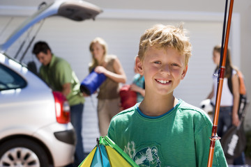 Family loading camping equipment into parked car boot on driveway, focus on boy (8-10) carrying fishing rod and kite in foreground, smiling, portrait