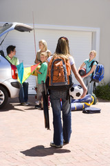 Family loading camping equipment into parked car boot on driveway, girl (11-13) carrying rucksack, soccer ball and tennis racquets in foreground, rear view