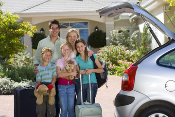 Family standing with luggage beside open boot of parked car on driveway, children (8-10) holding cuddly toys, smiling, portrait