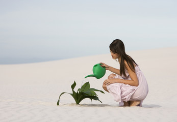 A woman watering a plant in the sand