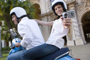 USA, California, San Diego, Balboa Park, couple riding on blue motor scooter, woman filming with portable video recorder, smiling, side view, portrait (tilt)