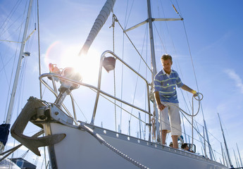 Man standing on deck of moored sailing boat, holding rope (lens flare)