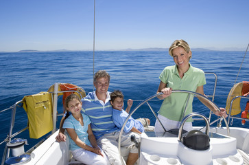 Family relaxing on deck of sailing boat out at sea, mother standing at helm, steering, smiling, portrait