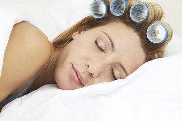 Young woman sleeping with curlers in hair