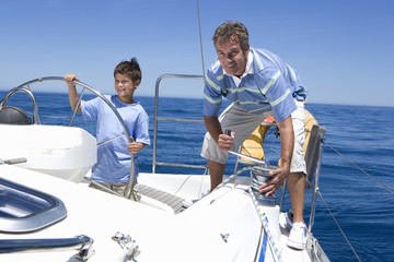 Father and son (8-10) standing on deck of sailing boat out to sea, boy steering, man winding rope pulley of boat rigging, smiling