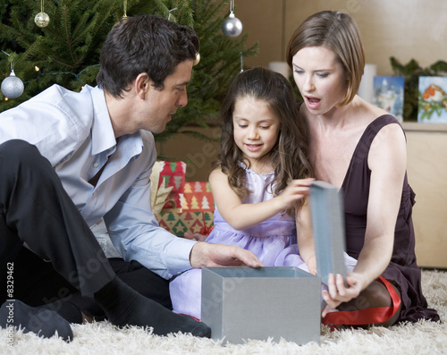 A couple and their young daughter opening Christmas presents