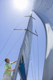Man standing on deck of sailing boat out to sea, adjusting sail mast rigging, side view, low angle view (lens flare)