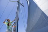 Father and son (8-10) standing on deck of sailing boat, adjusting sail mast rigging, side view, low angle view