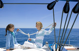 Mother and daughter (8-10) sitting at stern of sailing boat out at sea, tying knots in rope, smiling, profile