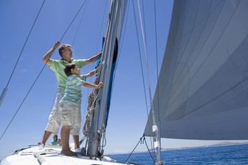 Father and son (8-10) standing on deck of sailing boat out to sea, adjusting sail mast rigging, side view